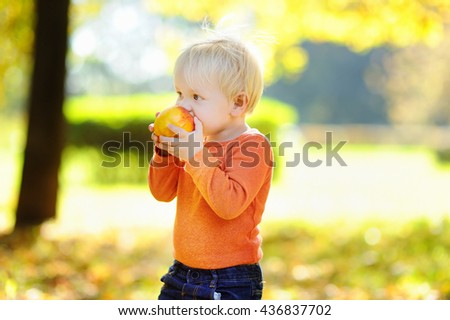 Beautiful toddler boy eating fresh bio peach outdoors