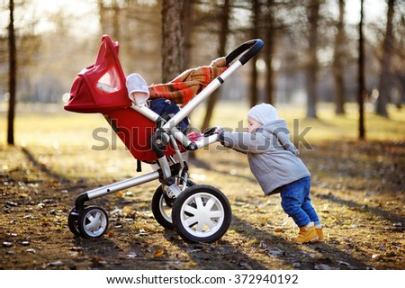 Beautiful toddler boy playing with his stroller walking outdoors at the warm spring day