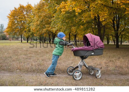 Beautiful toddler boy playing with modern stroller walking outdoors at the warm autumn day