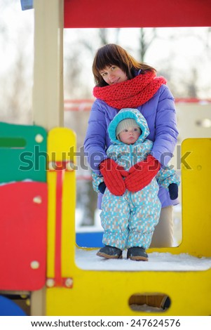 Beautiful toddler boy with his young mother on playground - stock photo