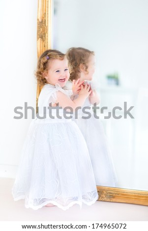 Beautiful toddler girl in a white dress standing next to a big mirror - stock photo
