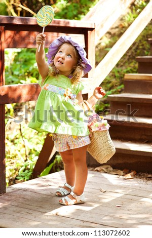 Beautiful toddler girl in hat eating lollipop in summer park with basket - stock photo