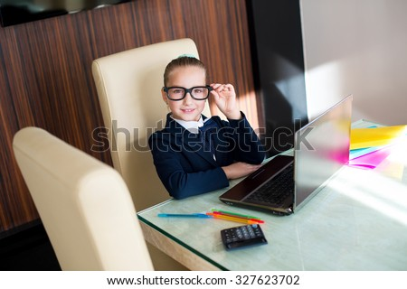 Beautiful toddler smart school girl in glasses sitting at table with laptop doing her home work - stock photo