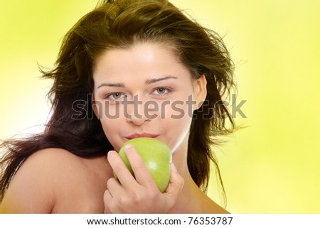 Beautiful topless girl with green apple,  over green background
