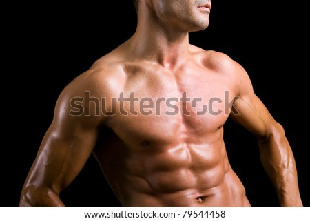 Beautiful torso of a young muscular man against black background - stock photo
