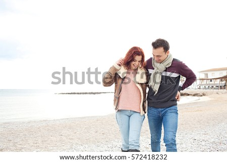 Beautiful tourist couple on winter break holiday in coastal beach destination, walking and hugging, recreation lifestyle outdoors. Seasonal travel vacation. Boyfriend and girlfriend smiling together.