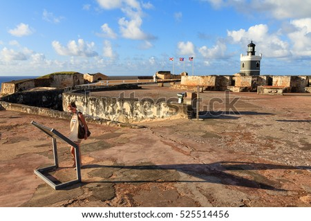 Beautiful tourist reads a sign at Fort San Felipe Del Morro in San Juan, Puerto Rico