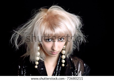beautiful tousled blonde in shiny black cape and pearl earrings - stock photo