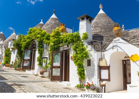 Beautiful town of Alberobello with trulli houses among green plants and flowers, main touristic district, Apulia region, Southern Italy - stock photo