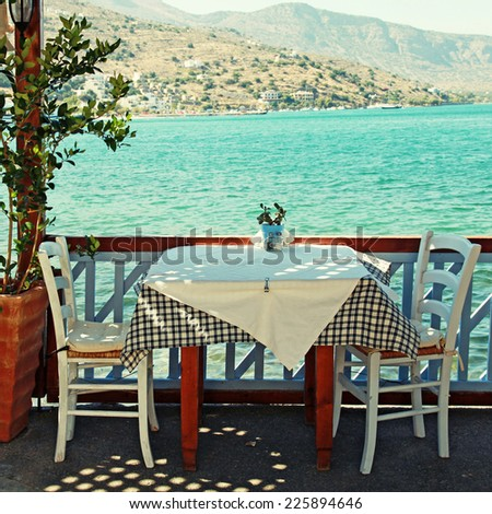 Beautiful traditional greek outdoor restaurant on terrace overlooking Mediterranean sea (Crete, Greece ). square toned image, instagram effect - stock photo