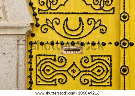 Beautiful traditional yellow door of Tunisia with black ornaments - stock photo