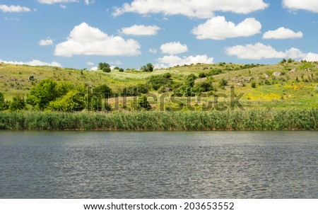 Beautiful tranquil scenic lake fringed with reeds backed by rolling green hills under a sunny blue sky with fluffy white clouds - stock photo