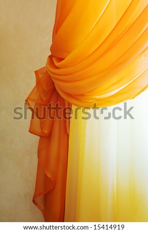 Beautiful translucent orange curtains in an apartment - stock photo