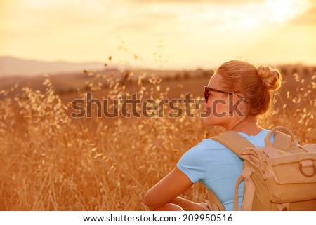 Beautiful traveler girl enjoying golden wheat field in sunset light, beautiful summer nature, farmland in Europe, travel and tourism concept  - stock photo