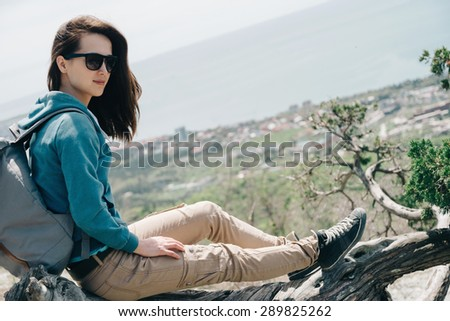 Beautiful traveler young woman resting on tree above the sea in summer - stock photo