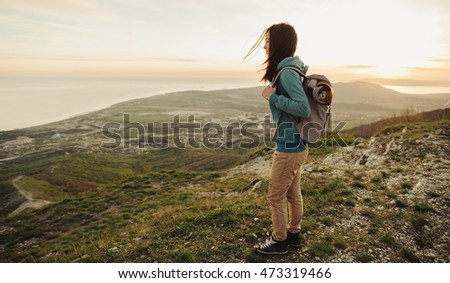 Beautiful traveler young woman with backpack walking in mountains at sunset