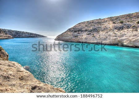Beautiful tropical bay on the island of Crete bordered on either side by rocky cliffs as the turquoise blue water enters the sheltered inlet with the hot summer sun reflecting across the sea - stock photo