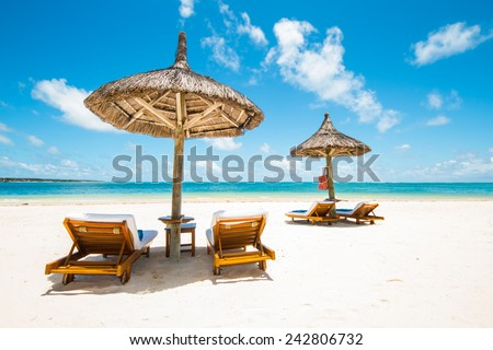 beautiful tropical beach with green coconut palms straw sunshades and wooden sunbeds in front of a turquoise sea with a blue sky, Mauritius, Africa  - stock photo