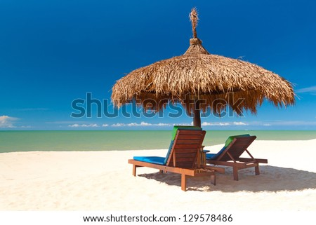 Beautiful tropical beach with parasol in Thailand - stock photo