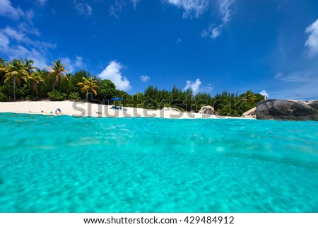 Beautiful tropical beach with white sand, turquoise ocean water and blue sky at Virgin Gorda, British Virgin Islands in Caribbean - stock photo
