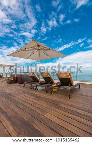 Beautiful tropical, caribbean wooden, flooring deck with lounges and beach umbrella at the ocean beach, resort.
