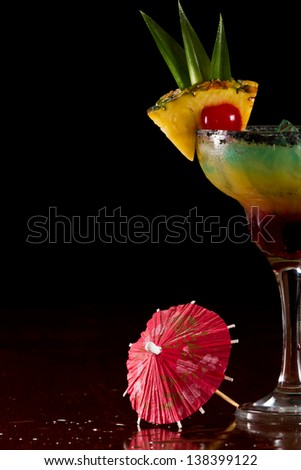 beautiful tropical cocktail served in a margarita glass with black salt on the rim and a pineapple slice with a cherry in it - stock photo