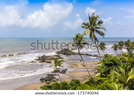 Beautiful tropical nature of Vagator Beach: palms, perfectly clear Arabian sea, golden sea beach, blue sky - one of busiest places and tourist attraction places of rest. Vagator Beach, Goa, India. - stock photo