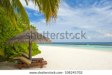 Beautiful tropical paradise in Maldives with coco palms hanging over the white and turquoise sea. Parasol is in the front. - stock photo