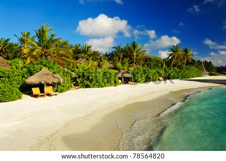 Beautiful tropical paradise in Maldives with coco palms hanging over the white beach, cozy bungalows and turquoise sea - stock photo