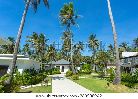Beautiful tropical resort bungalows under the palm trees - stock photo