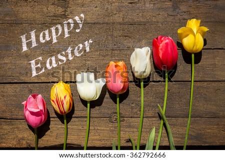 beautiful tulips on a brown wooden table and text Happy easter, greeting card - stock photo