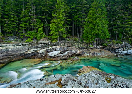 Beautiful turquoise blue water flowing in McDonald Creek in Glacier National Park, Montana, USA. - stock photo