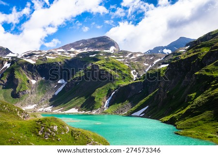 beautiful turquoise lake below the high mountains with snow on