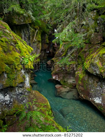 Beautiful turquoise mountain stream among mossy green boulders in Glacier National Park, Montana. - stock photo