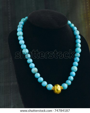 Beautiful turquoise necklace decorated by gold - stock photo