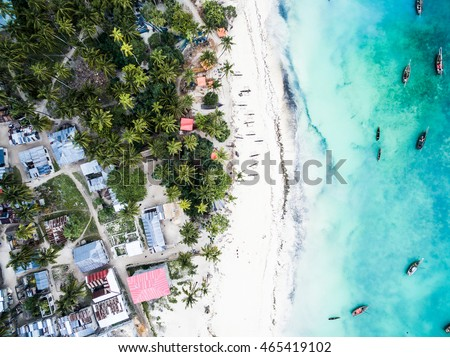 beautiful turquoise ocean meets african island with houses and palms on Zanzibar, aerial photo, top view