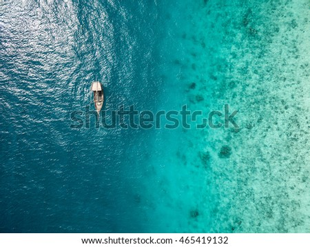 beautiful turquoise ocean water with boat on it top view aerial photo