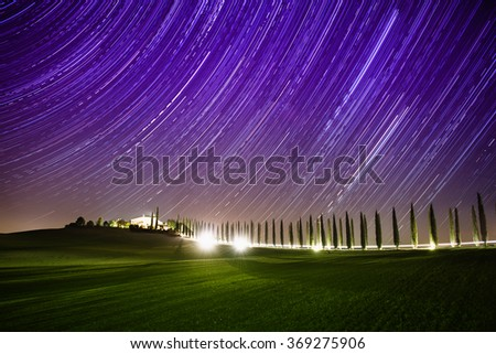 Beautiful Tuscany night landscape with star trails on the sky, cypresses and shining road in green meadow. Natural outdoor amazing fantasy background. - stock photo