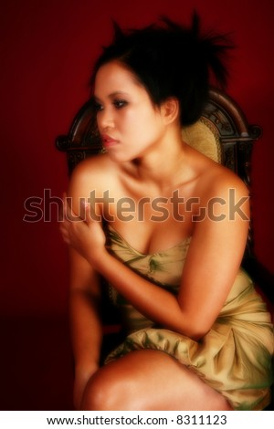 Beautiful twenty something Asian Indonesian mixed womn in gold formal dress on crimson red background.