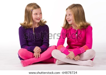 Beautiful twin girls playing together - stock photo