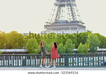Beautiful twin sisters in red and black polka dot dresses in front of the Eiffel tower in Paris, France - stock photo