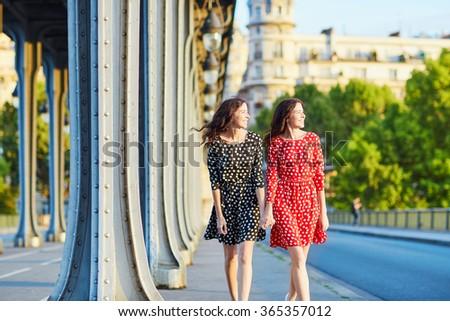 Beautiful twin sisters in red and black polka dot dresses on the Bir Hakeim bridge in Paris, France - stock photo