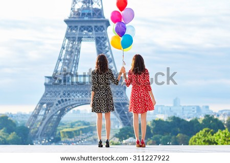 Beautiful twin sisters in red and black polka dot dresses with huge bunch of colorful balloons in front of the Eiffel tower in Paris, France - stock photo