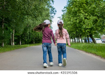 Beautiful twins walking on the street - stock photo