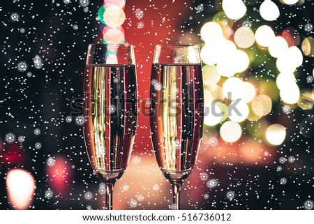 Beautiful two glasses of champagne standing on the table in the background of a blurred room with a decorated Christmas tree and fireplace, and with stars and snow.