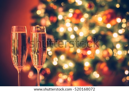 Beautiful two glasses of champagne standing on the table in the background of a blurred room with a decorated Christmas tree and fireplace