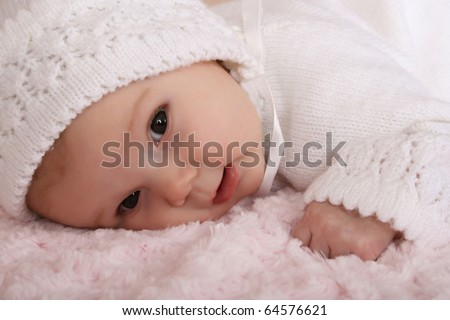 Beautiful two month old baby girl wearing a knitted outfit - stock photo