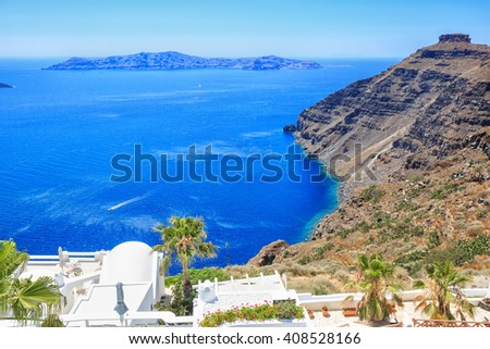 Beautiful typical white greek buildings with different flowers and palm. Sea side of Thira, Santorini island, Greece - stock photo