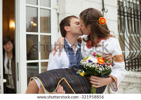 beautiful ukrainian bride and groom in native embroidery suits kissing, traditional wedding ceremony