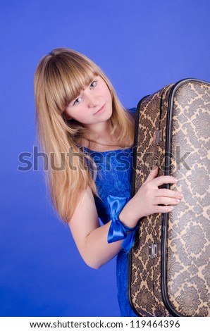 beautiful Ukrainian woman with suitcase isolated on a blue background